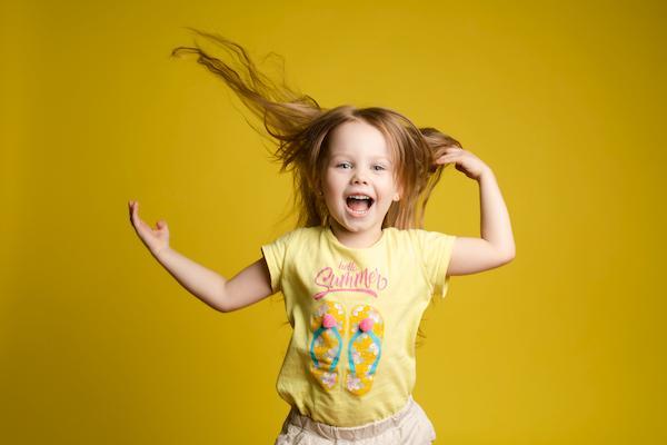 طفلة تمسك شعرها وهي سعيدة